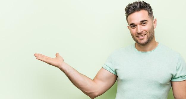 Junger hübscher mann gegen einen grünen hintergrund, der einen kopienraum auf einer handfläche zeigt und eine andere hand auf taille hält.