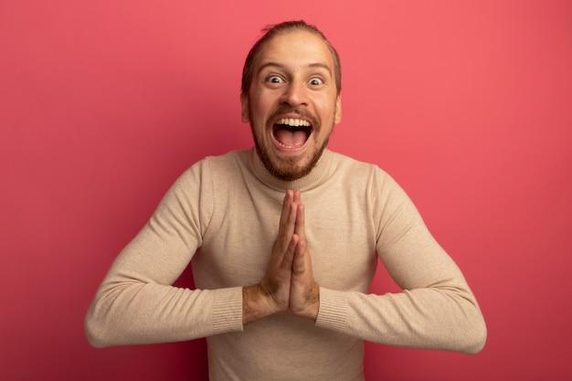 Junger hübscher mann im beige rollkragenpullover, der hände zusammenhält wie namaste geste glücklich und aufgeregt, die über rosa wand stehen