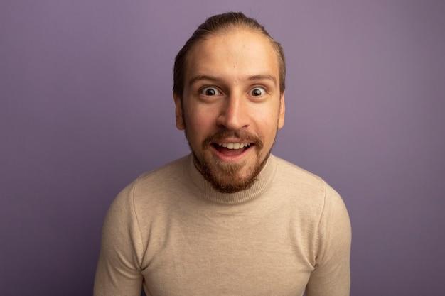 Junger hübscher mann im beige rollkragenpullover überrascht und glücklich