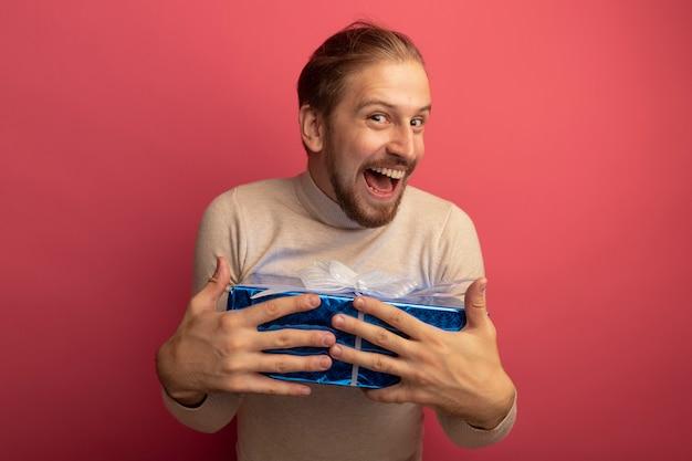 Junger hübscher mann im beigen rollkragenpullover, der geschenkbox glücklich und aufgeregt hält über rosa wand hält