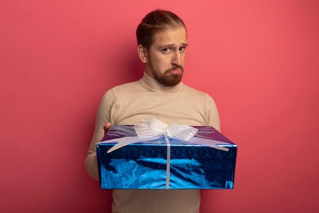 Junger hübscher mann im beigen rollkragenpullover, der geschenkbox mit traurigem cobfuse-ausdruck hält