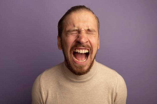 Junger hübscher mann im beigen rollkragenpullover, der mit traurigem und hoffnungslosem ausdruck hart weint