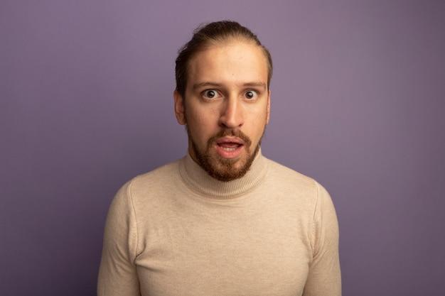 Junger hübscher mann im beigen rollkragenpullover, der vorne besorgt über lila wand steht