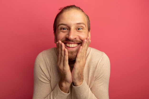 Junger hübscher mann im beigen rollkragenpullover glücklich und überrascht breit lächelnd