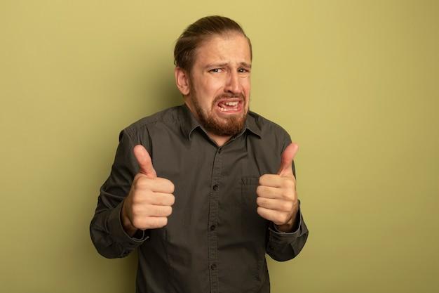 Junger hübscher mann im grauen hemd besorgt und gereizt, daumen hoch zeigend Kostenlose Fotos