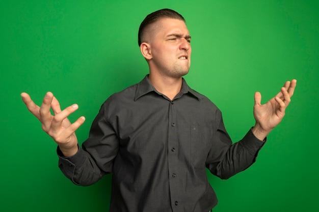 Junger hübscher mann im grauen hemd, das beiseite schaut, wobei arme aut verwirrt und unzufrieden sind, die über grüner wand stehen