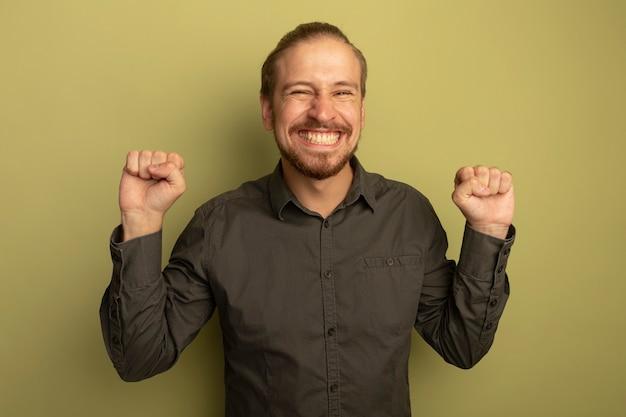 Junger hübscher mann im grauen hemd, das die fäuste ballt, glücklich und aufgeregt, seinen erfolg freudig