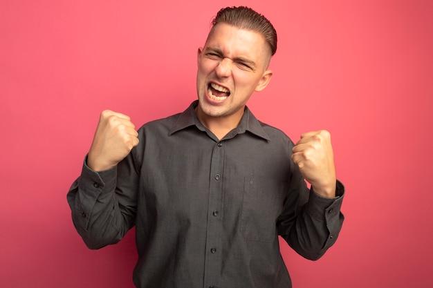 Junger hübscher mann im grauen hemd, das fäuste ballt glücklich und aufgeregt schreit, die über rosa wand stehen