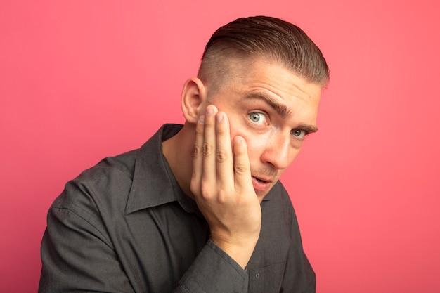 Junger hübscher mann im grauen hemd, das front betrachtet, verwirrt mit arm auf seiner wange, die über rosa wand steht