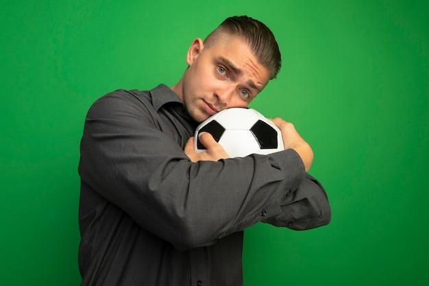 Junger hübscher mann im grauen hemd, das fußball umarmt, der seinen kopf auf ball lehnt, der vorne mit traurigem ausdruck steht, der über grüner wand steht