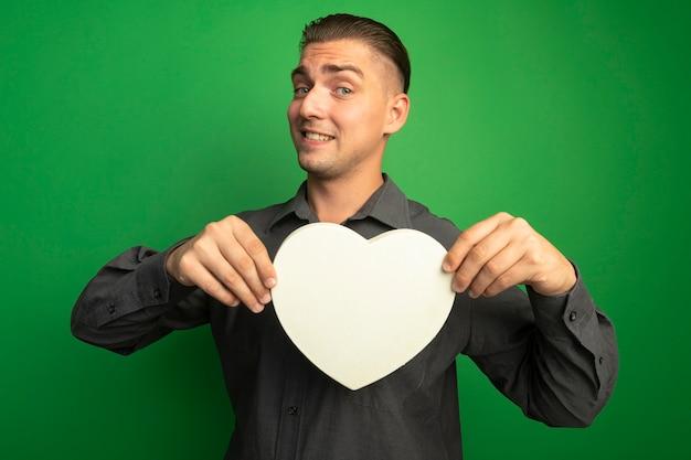 Junger hübscher mann im grauen hemd, das pappherz zeigt, das vorne lächelnd mit glücklichem gesicht über grüner wand steht