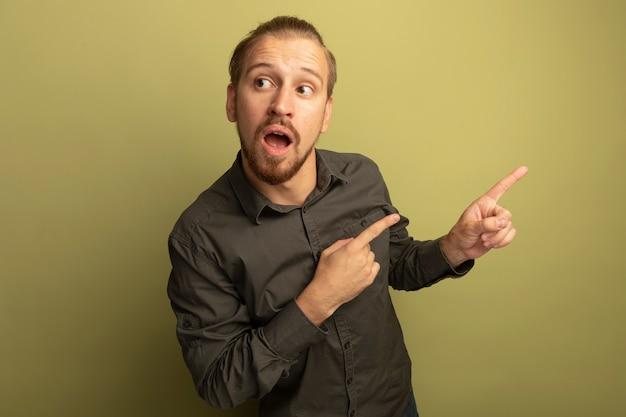 Junger hübscher mann im grauen hemd, das verwirrt zeigt und mit zeigefingern zur seite zeigt