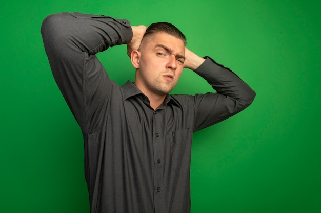 Junger hübscher mann im grauen hemd, das vorne mit ernstem selbstbewusstem ausdruck mit händen hinter seinem kopf betrachtet, die über grüner wand stehen