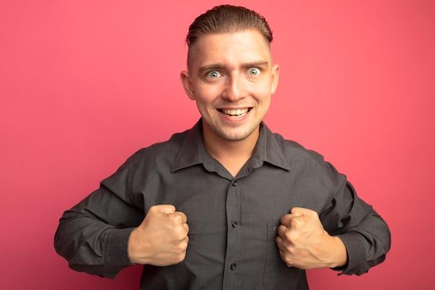 Junger hübscher mann im grauen hemd, das vorne mit geballten fäusten glücklich und aufgeregt über rosa wand steht