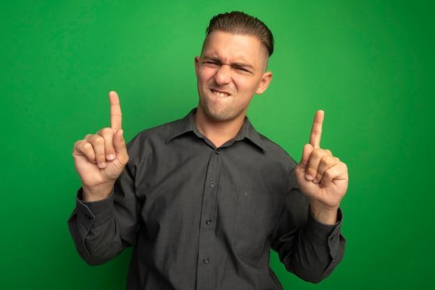 Junger hübscher mann im grauen hemd, das zuversichtlich und glücklich zeigt zeigefinger zeigt