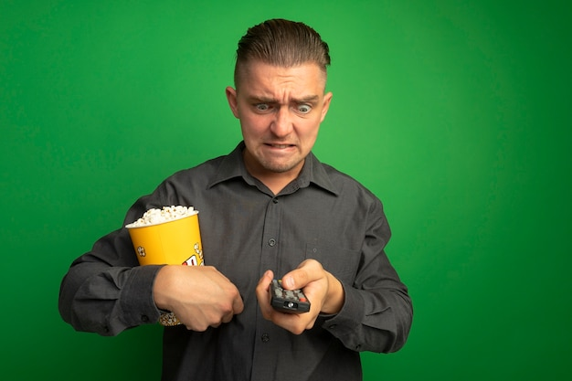 Junger hübscher mann im grauen hemd, der eimer mit popcorn unter verwendung der tv-fernbedienung hält, die ihn mit dem wütenden gesicht betrachtet, das wild über grüner wand steht