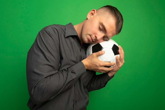 Junger hübscher mann im grauen hemd, der fußball hält, der seinen kopf auf ball mit geschlossenen augen lehnt