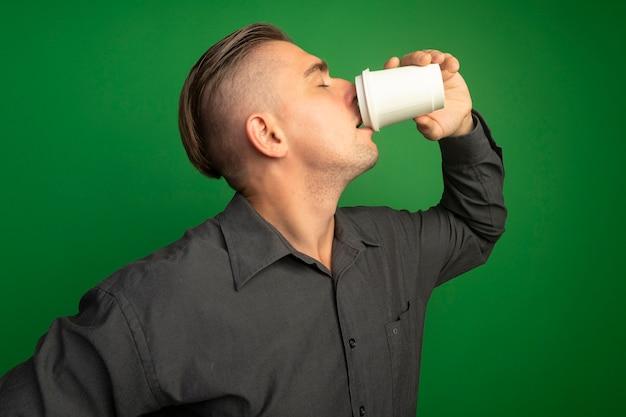 Junger hübscher mann im grauen hemd, der pappbecher trinkt, der kaffee über grüner wand steht