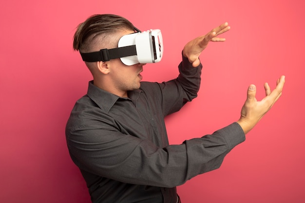 Junger hübscher mann im grauen hemd mit der brille der virtuellen realität, die beiseite schaut und mit den händen steht, die über rosa wand stehen