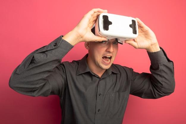 Junger hübscher mann im grauen hemd mit der brille der virtuellen realität, die vorne lächelnd aufgeregt und glücklich steht über rosa wand schaut