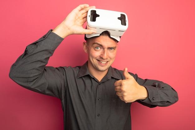 Junger hübscher mann im grauen hemd mit der brille der virtuellen realität, die vorne lächelnd mit glücklichem gesicht schaut, das daumen oben steht über rosa wand zeigt