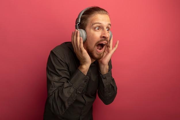 Junger hübscher mann im grauen hemd mit kopfhörern auf seinem kopf, der erstaunt und überrascht beiseite schaut