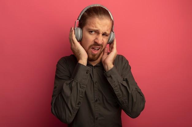 Junger hübscher mann im grauen hemd mit kopfhörern auf seinem kopf, der missfallen beiseite schaut