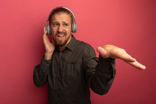 Junger hübscher mann im grauen hemd mit kopfhörern auf seinem kopf, der mit ausgestrecktem arm unzufrieden aussieht