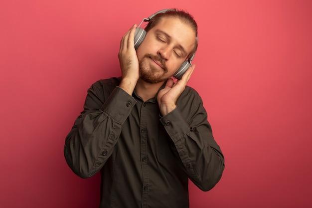 Junger hübscher mann im grauen hemd mit kopfhörern auf seinem kopf, der seine lieblingsmusik mit geschlossenen augen genießt