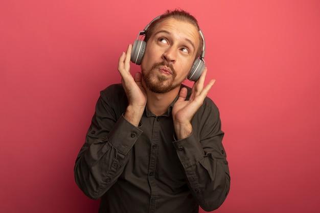 Junger hübscher mann im grauen hemd mit kopfhörern auf seinem kopf, der verwirrt oben schaut