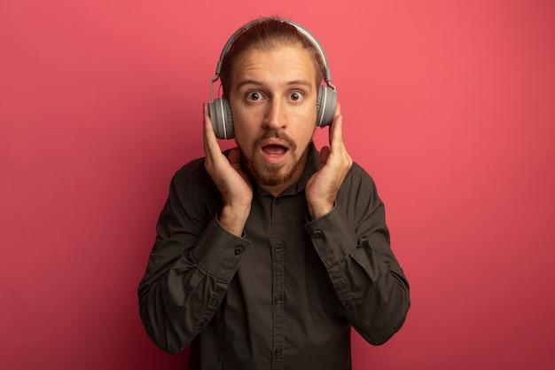 Junger hübscher mann im grauen hemd mit kopfhörern auf seinem kopf erstaunt und überrascht