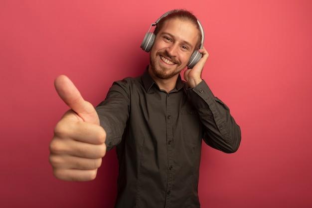 Junger hübscher mann im grauen hemd mit kopfhörern auf seinem kopf lächelnd mit glücklichem gesicht, das daumen oben zeigt