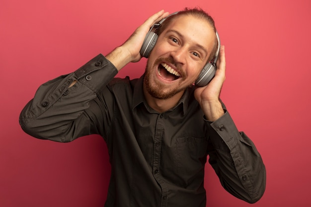 Junger hübscher mann im grauen hemd mit kopfhörern auf seinem kopf lächelnd mit glücklichem gesicht
