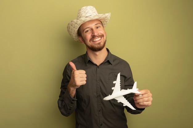 Junger hübscher mann im grauen hemd und im sommerhut, der spielzeugflugzeug glücklich und positiv lächelnd fröhlich zeigt daumen oben hält