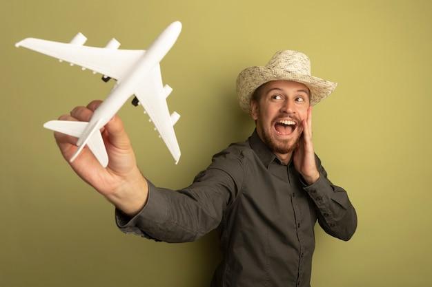 Junger hübscher mann im grauen hemd und im sommerhut, der spielzeugflugzeug hält, das es glücklich und aufgeregt betrachtet