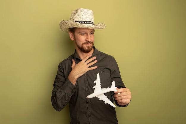 Junger hübscher mann im grauen hemd und im sommerhut, der spielzeugflugzeug hält, das mit hand auf seiner brust beiseite schaut und sich dankbar fühlt