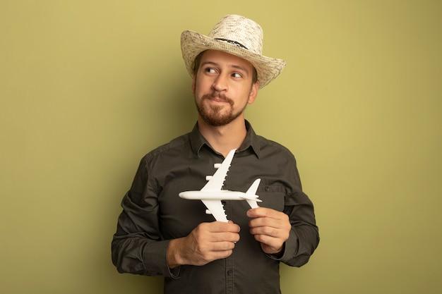 Junger hübscher mann im grauen hemd und im sommerhut, der spielzeugflugzeug hält, das mit schüchternem lächeln auf gesicht beiseite schaut