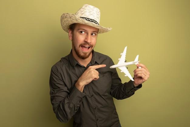 Junger hübscher mann im grauen hemd und im sommerhut, der spielzeugflugzeug hält, das mit zeigefinger glücklich und positiv zeigt
