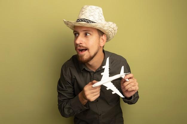 Junger hübscher mann im grauen hemd und im sommerhut, der spielzeugflugzeug hält, das schlau lächelnd beiseite schaut