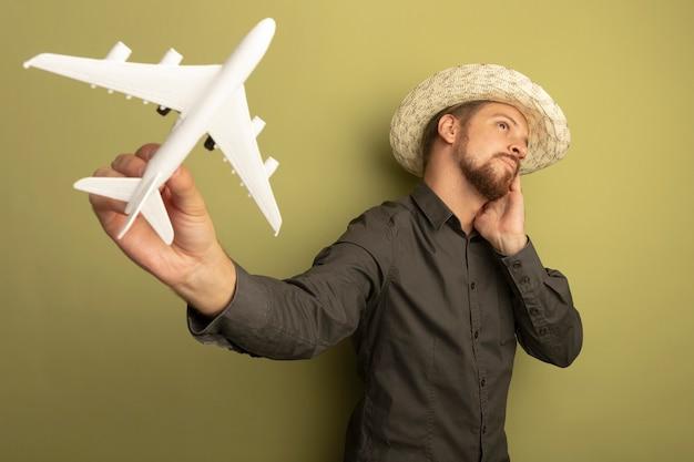 Junger hübscher mann im grauen hemd und im sommerhut, der spielzeugflugzeug hält, das verwirrt beiseite schaut