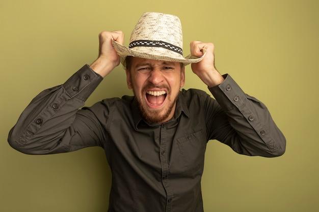 Junger hübscher mann im grauen hemd und im sommerhut, die mit aggressivem ausdruck schreien, der seinen hut berührt