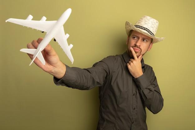 Junger hübscher mann im grauen hemd und im sommerhut, die spielzeugflugzeug halten, schauen es mit nachdenklichem ausdruck auf gesichtsdenken an