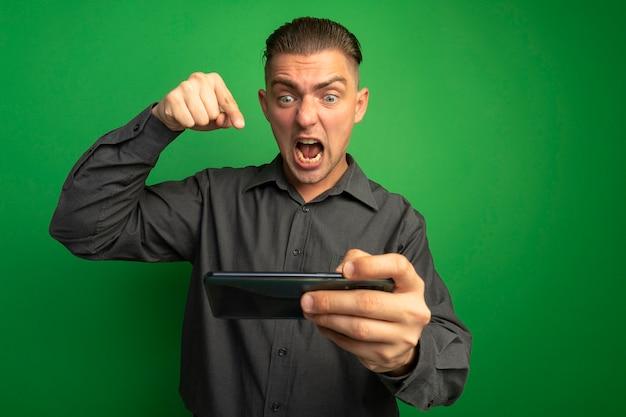 Junger hübscher mann im grauen hemd unter verwendung der geballten faust des gadgets, die verrückte amd und wütendes geschrei bündelt, das über grüner wand steht