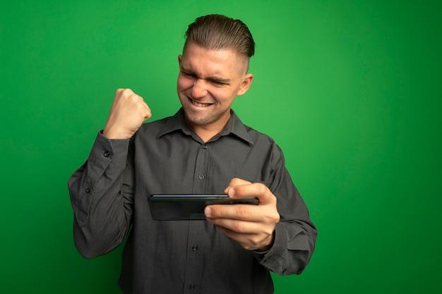 Junger hübscher mann im grauen hemd unter verwendung der geballten faust des gadgets, glücklich und aufgeregt, seinen erfolg freudig stehend über grüner wand freudig