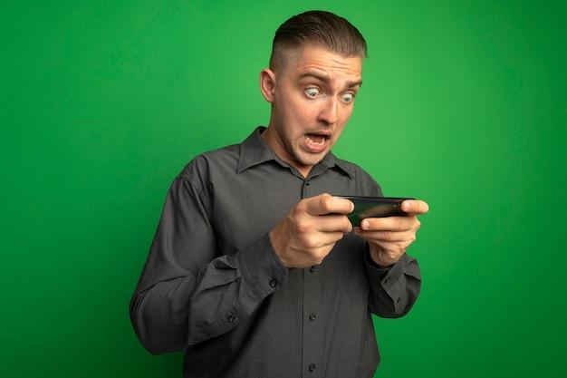 Junger hübscher mann im grauen hemd unter verwendung des smartphones, das über grüner wand überrascht und erstaunt steht