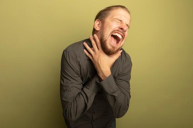 Junger hübscher mann im grauen hemd würgt händchenhalten in panik an seiner kehle