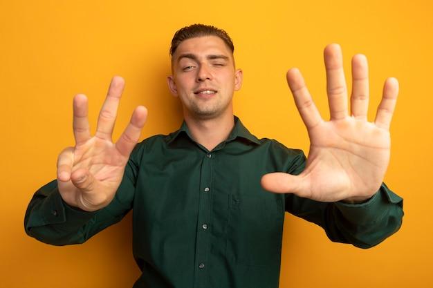 Junger hübscher mann im grünen hemd, das mit dem finger nummer acht zeigt und oben zeigt, der zuversichtlich lächelt