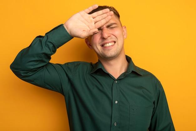 Junger hübscher mann im grünen hemd, der verwirrt mit der hand über seinem kopf tannenfehler sah, vergaß wichtige sache, die über orange wand steht