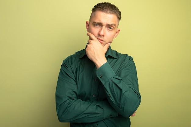 Junger hübscher mann im grünen hemd mit hand auf kinn denken