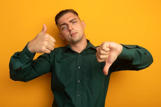 Junger hübscher mann im grünen hemd mit skeptischem ausdruck, der daumen oben und unten zeigt